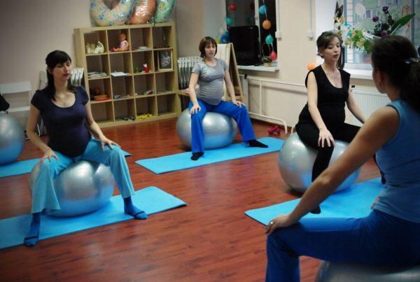 Женщины сидят на больших мячах на курсах для беременных