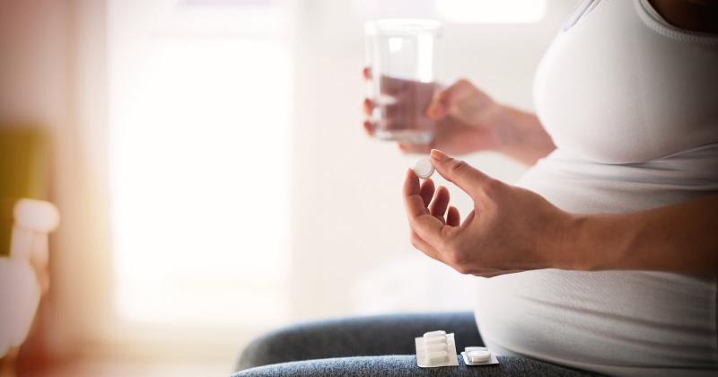 Беременная держит в одной руке таблетку, а в другой - стакан с водой