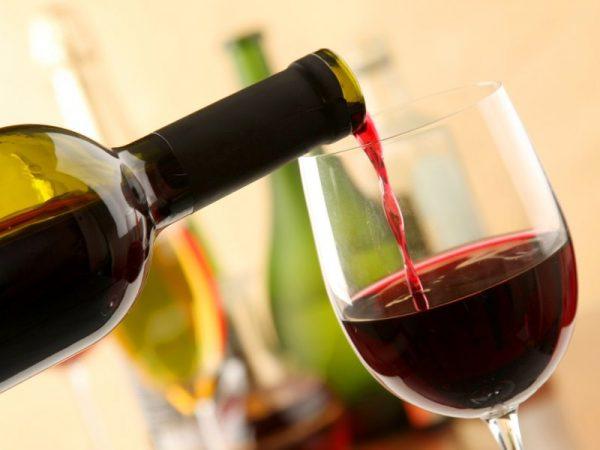 красное вино из бутылки льётся в бокал