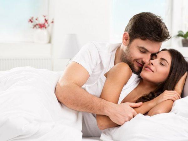 Мужчина лежит сзади женщины и обнимает её