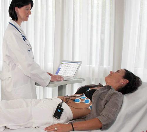 Фотография лежащей на кушетке женщины, рядом с которой стоит врач, фиксирующий результаты ЭКГ
