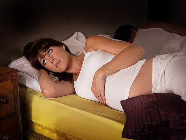 Беременная лежит ночью в постели с открытыми глазами, рядом спящий муж