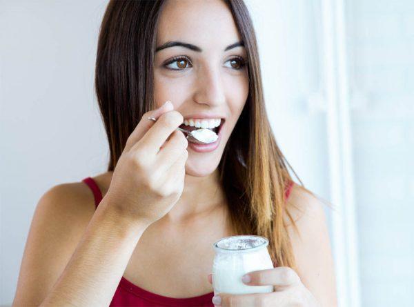 Девушка ест молочный продукт