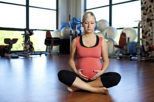 Беременная сидит на полу, согнув и скрестив ноги, и поддерживает руками живот снизу