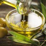 Оливковое масло из бутылки наливают в миску, рядом лежат оливки
