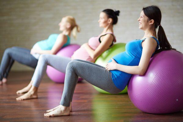 Беременные выполняют физические упражнения, опираясь спинами на мячи