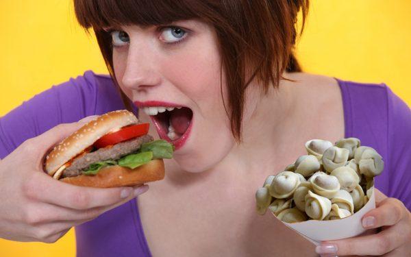 девушка подносит ко рту гамбургер
