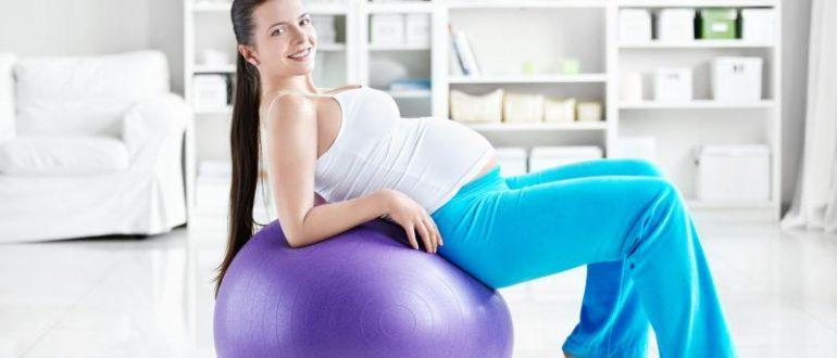 Беременная женщина опирается спиной и локтями на фитбол