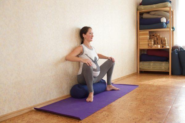Беременная женщина сидит на болстере у стены