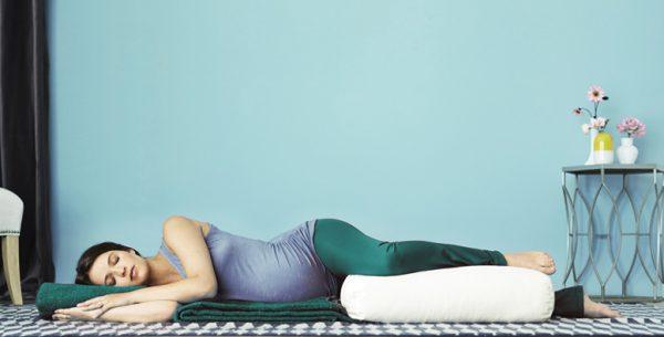 Беременная женщина лежит на боку