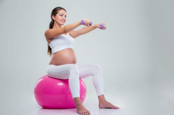 Беременная сидит на мяче и держит гантели в руках, вытянутых вперёд