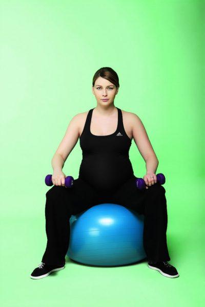 Беременная сидит на фитболе