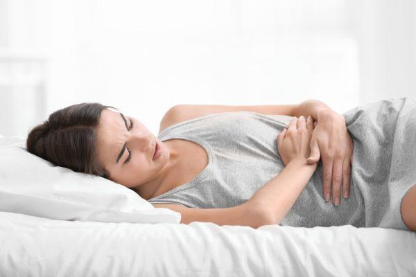 Женщина лежит на кровати и держится за живот