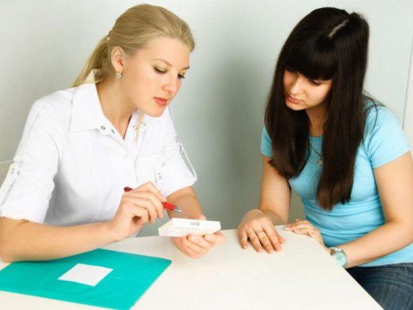 Женщина на приёме у врача, врач показывает ей упаковку лекарства