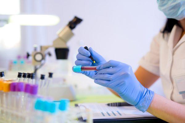 Лаборант держит пробирку с кровью