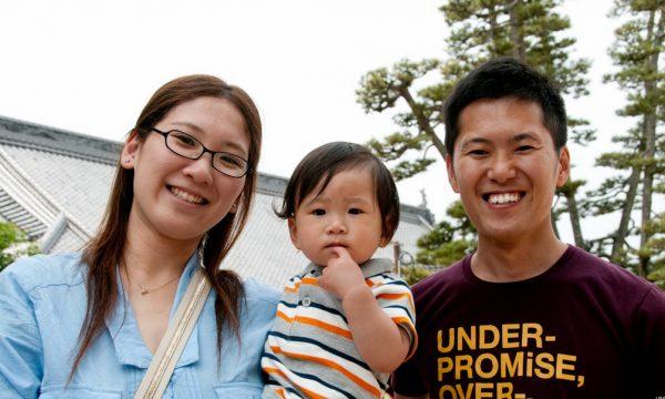 Улыбающиеся японские мужчина и женщина держат на руках мальчика