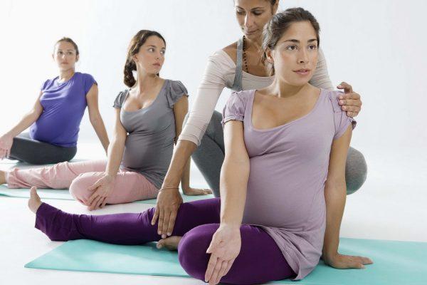 Беременные занимаются йогой с тренером