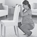Беременная держится за стул и садится на корточки