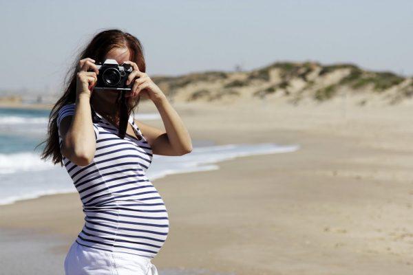 Беременная девушка фотографирует