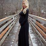 Девушка в чёрном платье на 22-й неделе беременности