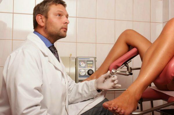 Женщина в гинекологическом кресле, рядом — врач