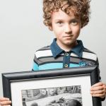 Маленький мальчик с фотографией себя новорождённого