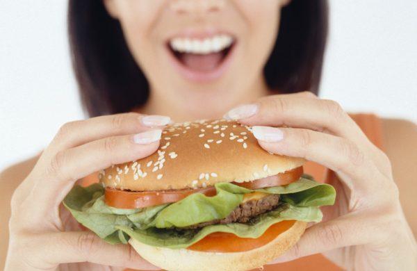 девушка с открытым ртом и гамбургером в руках
