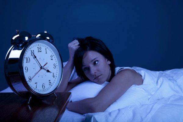 девушка лежит в кровати в тёмной комнате, глядя на часы