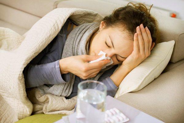 женщина лежит в постели, закутанная одеялом и с платком у носа