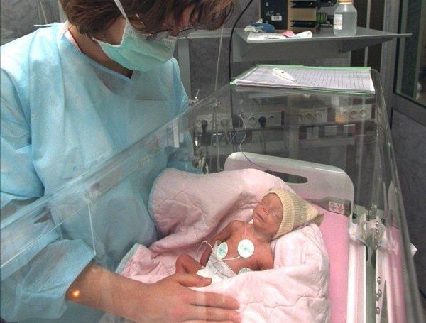Новорождённый в кувезе и врач