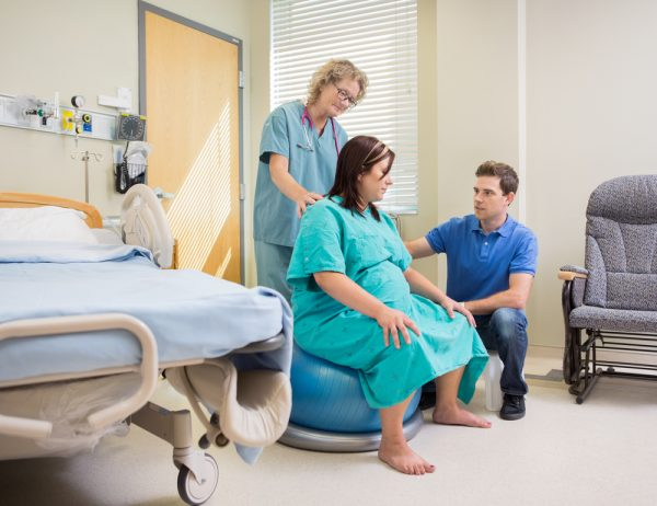Беременная на мяче рядом с мужем и врачом