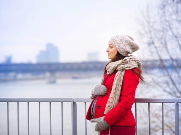 беременная зимой стоит на мосту