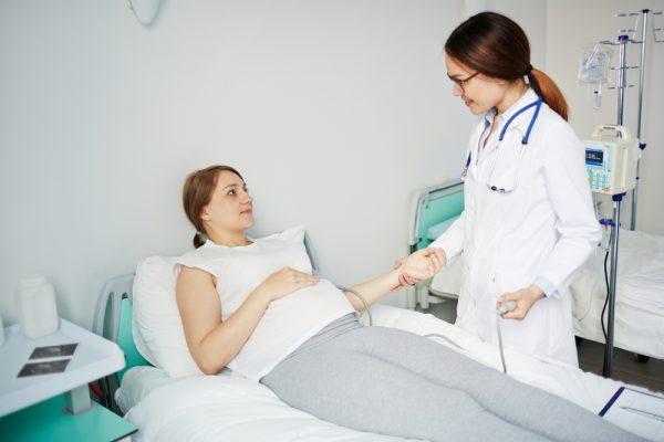 Беременная лежит в палате, рядом врач